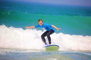 Adolescent qui surf une vague