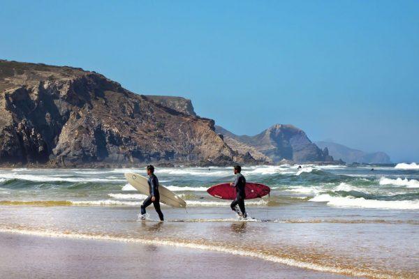 Deux surfeur marchent vers le rivage en tenant leur planche de surf