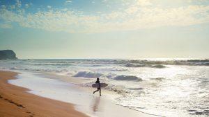 Jeune surfeur courant vers la mer