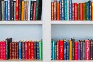 bibliothèque maison composée d'étagère blanches avec des livres de couleurs